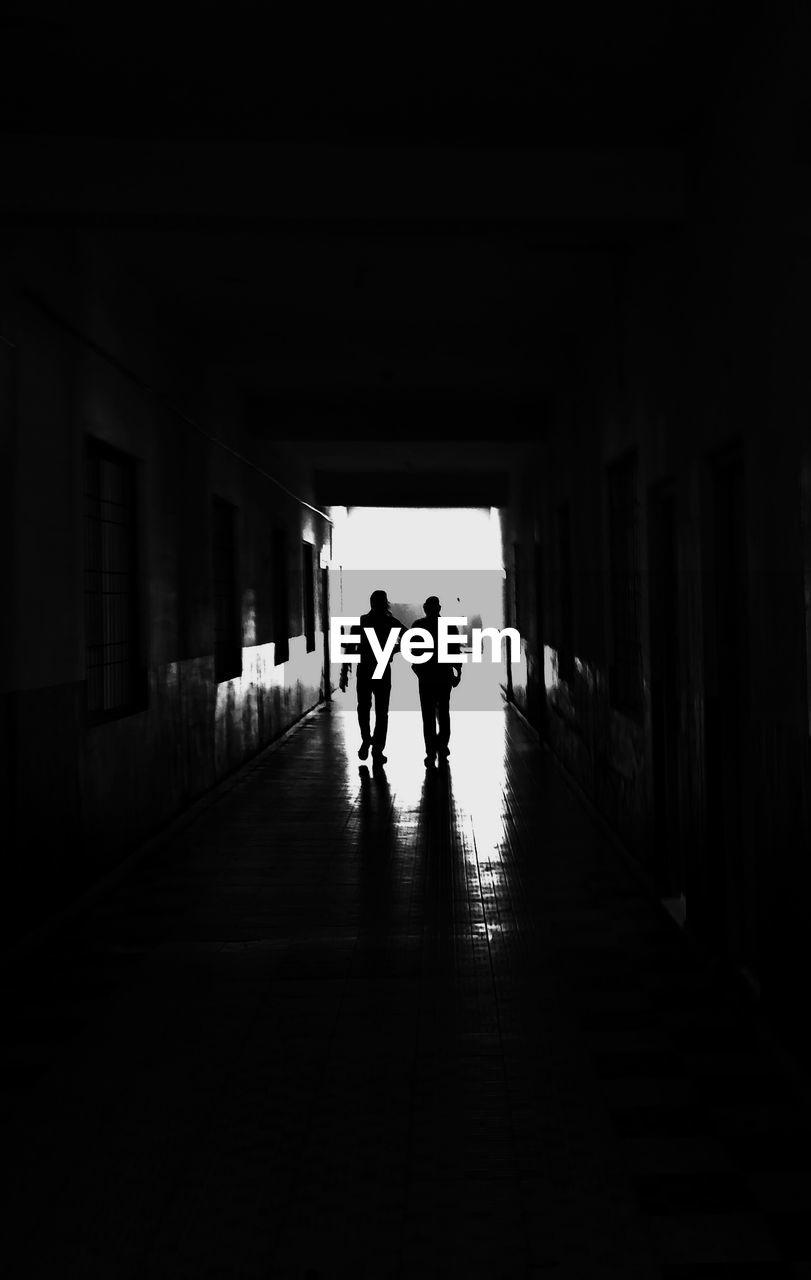 Silhouette Men Walking In Corridor Of Building