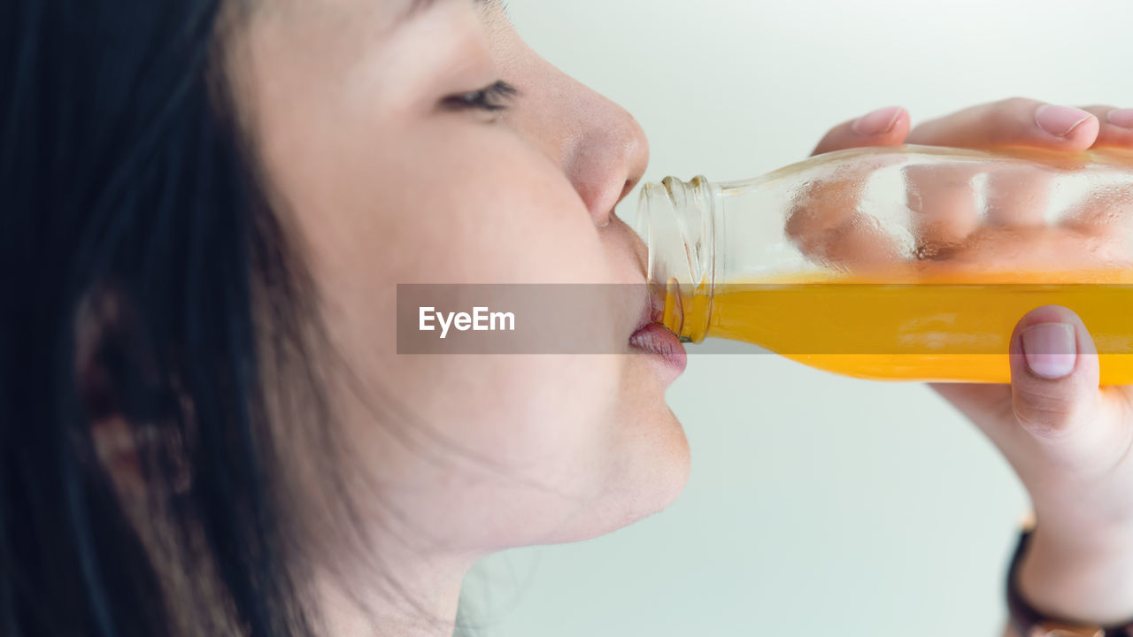 Close-Up Of Woman Drinking Juice From Bottle