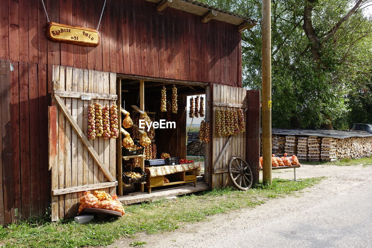 architecture, built structure, building exterior, food and drink, food, day, no people, building, nature, wood - material, house, outdoors, freshness, plant, hanging, store, large group of objects, tree, sunlight, agriculture, retail display