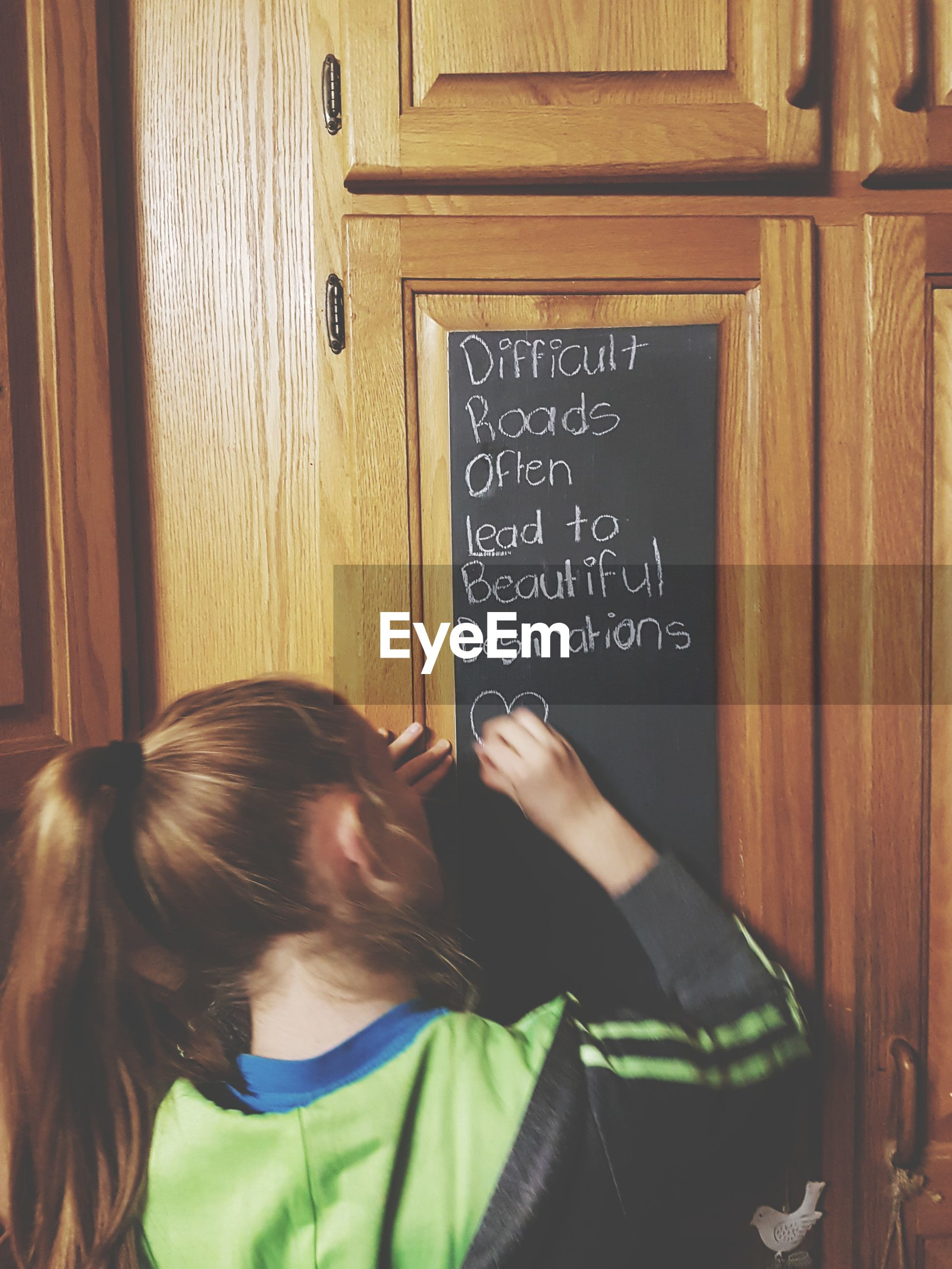Rear view of girl writing with chalk on door