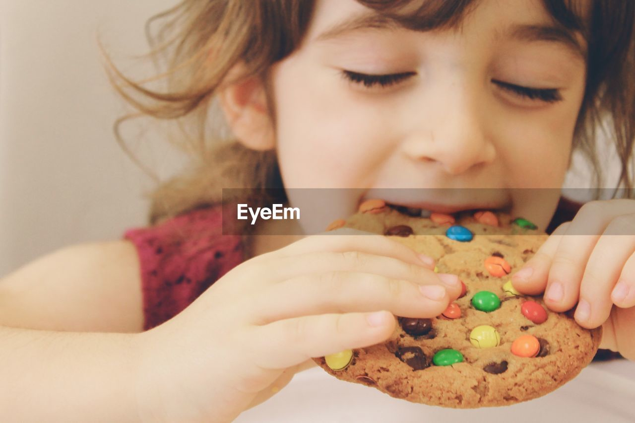 Cute girl eating cookie at home