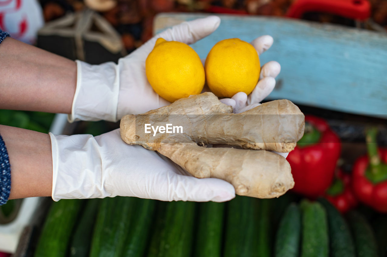 The concept of safe shopping  a woman in disposable gloves buys lemon and ginger. vitamin