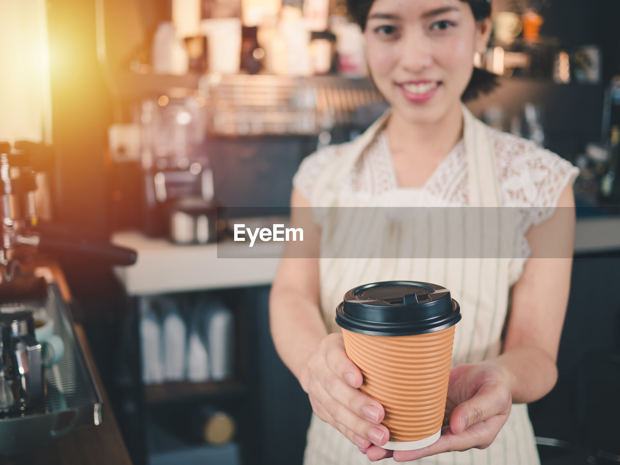 Portrait of woman holding disposable cup while standing in cafe