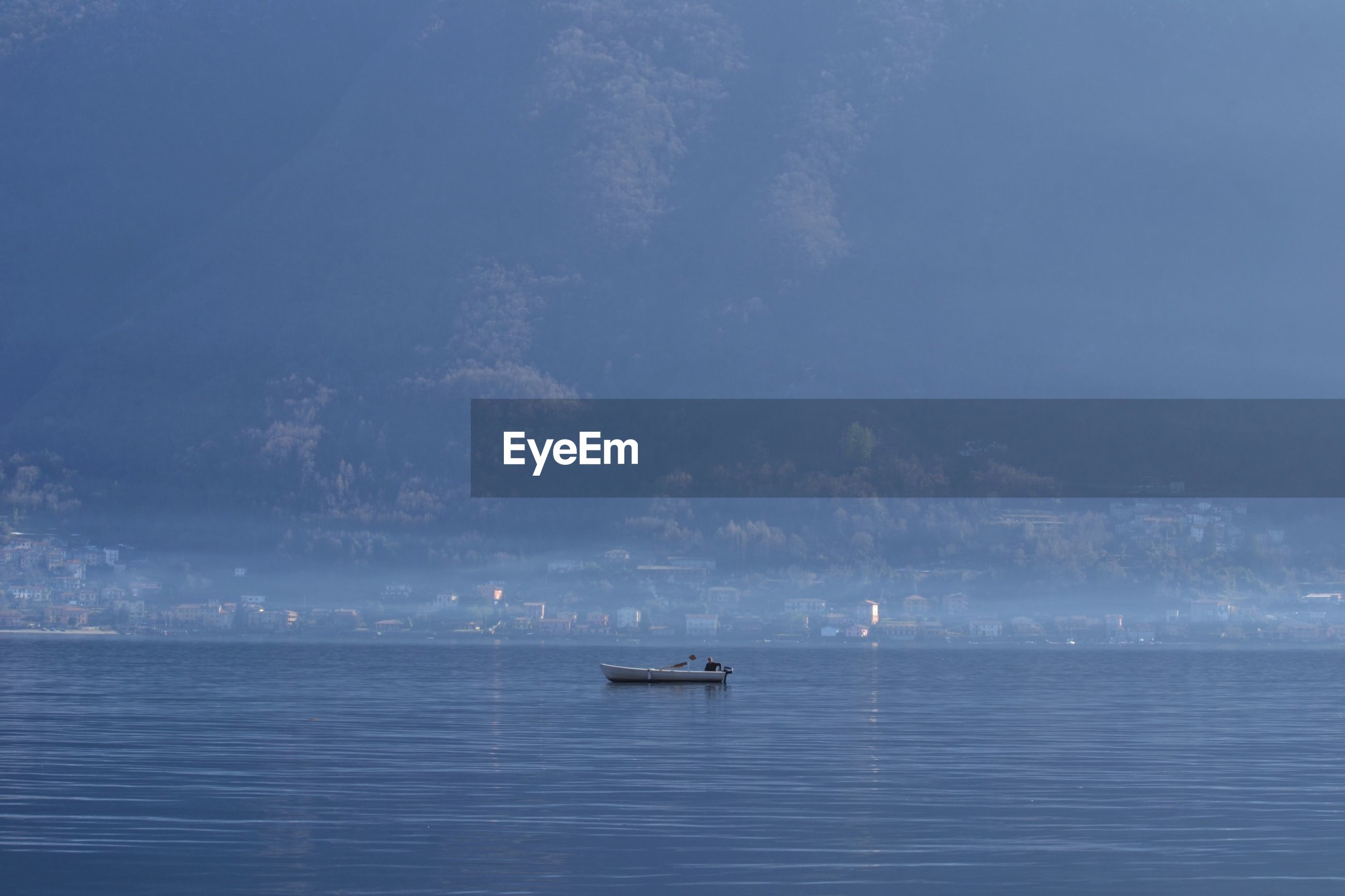 Boat in sea against trees during foggy weather