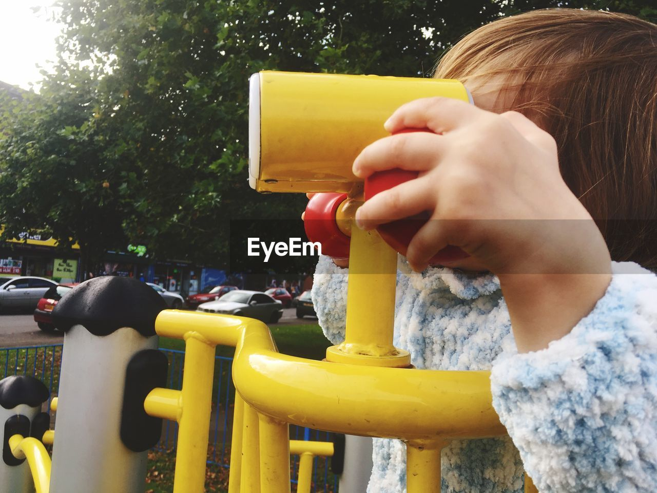 Close-up of girl on play equipment at park