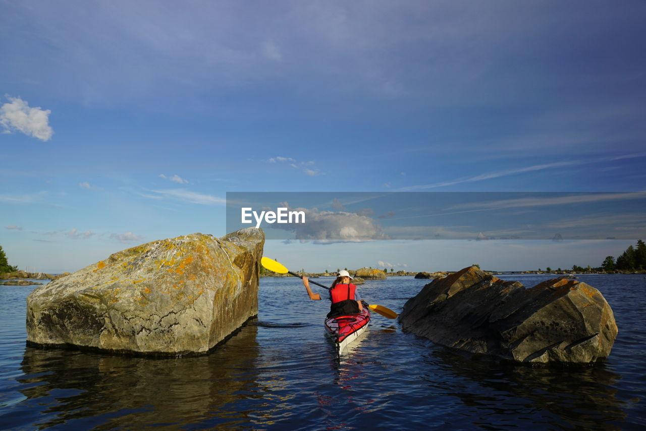 Woman On Kayak Against Cloudy Sky