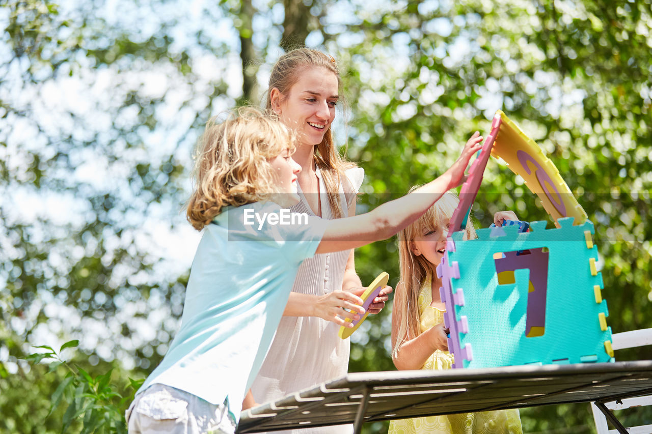 Happy family playing with toy on table