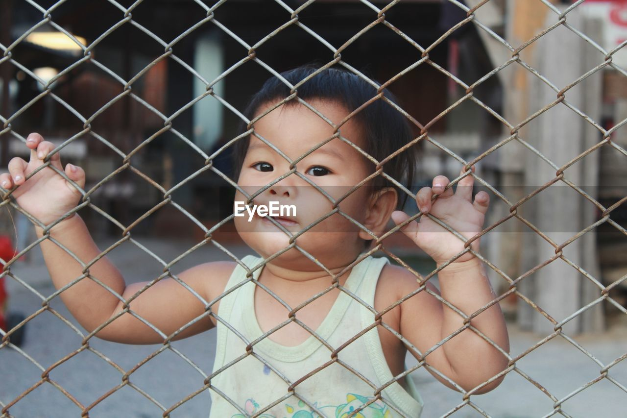 Portrait Of Cute Baby Girl Seen Through Fence