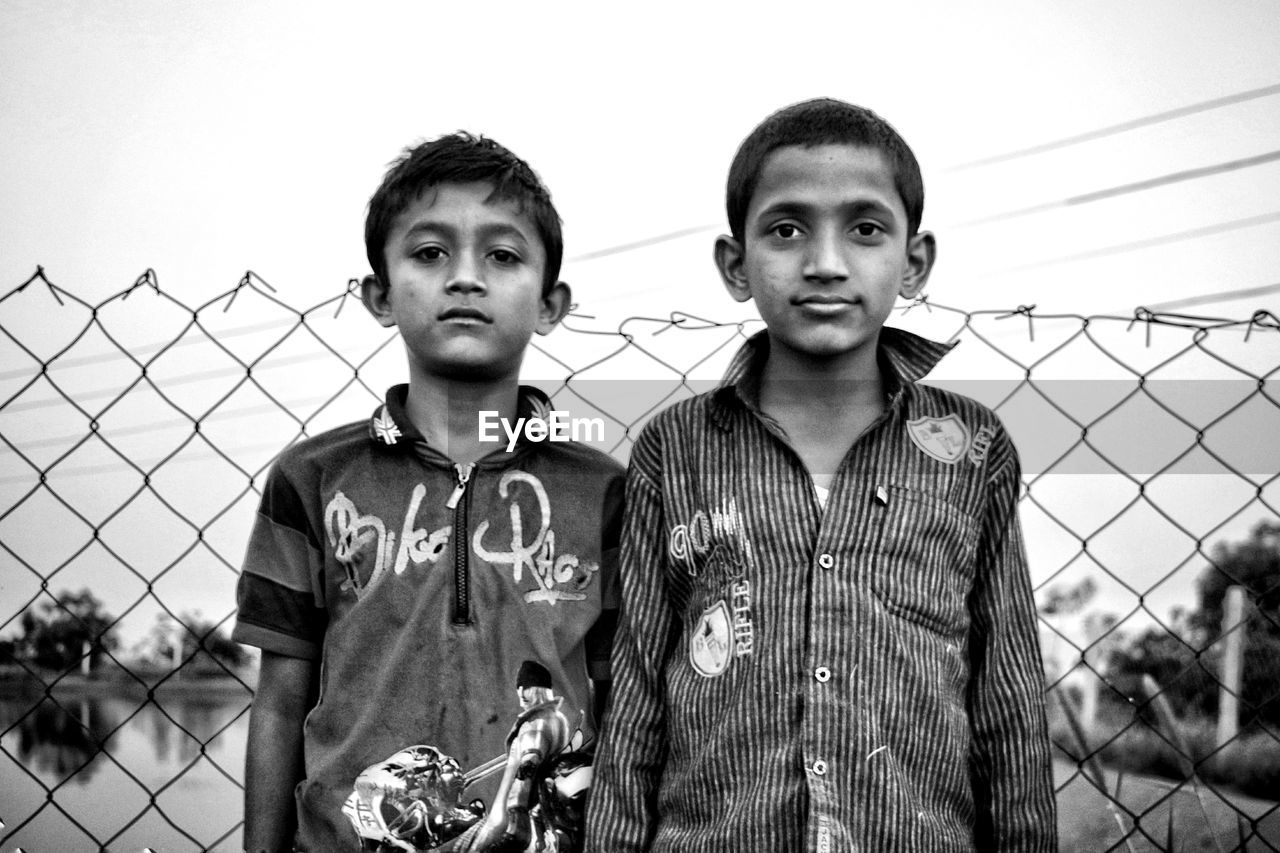 looking at camera, portrait, real people, fence, front view, barrier, men, boundary, child, lifestyles, leisure activity, standing, males, young men, casual clothing, sky, people, boys, young adult, togetherness