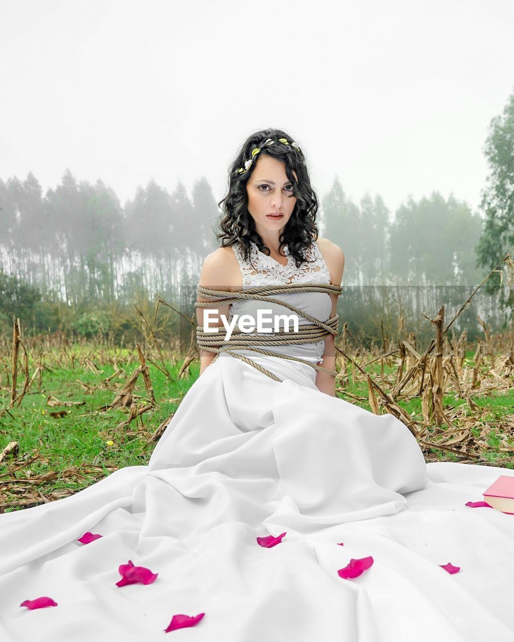 Portrait of bride tied with rope on field