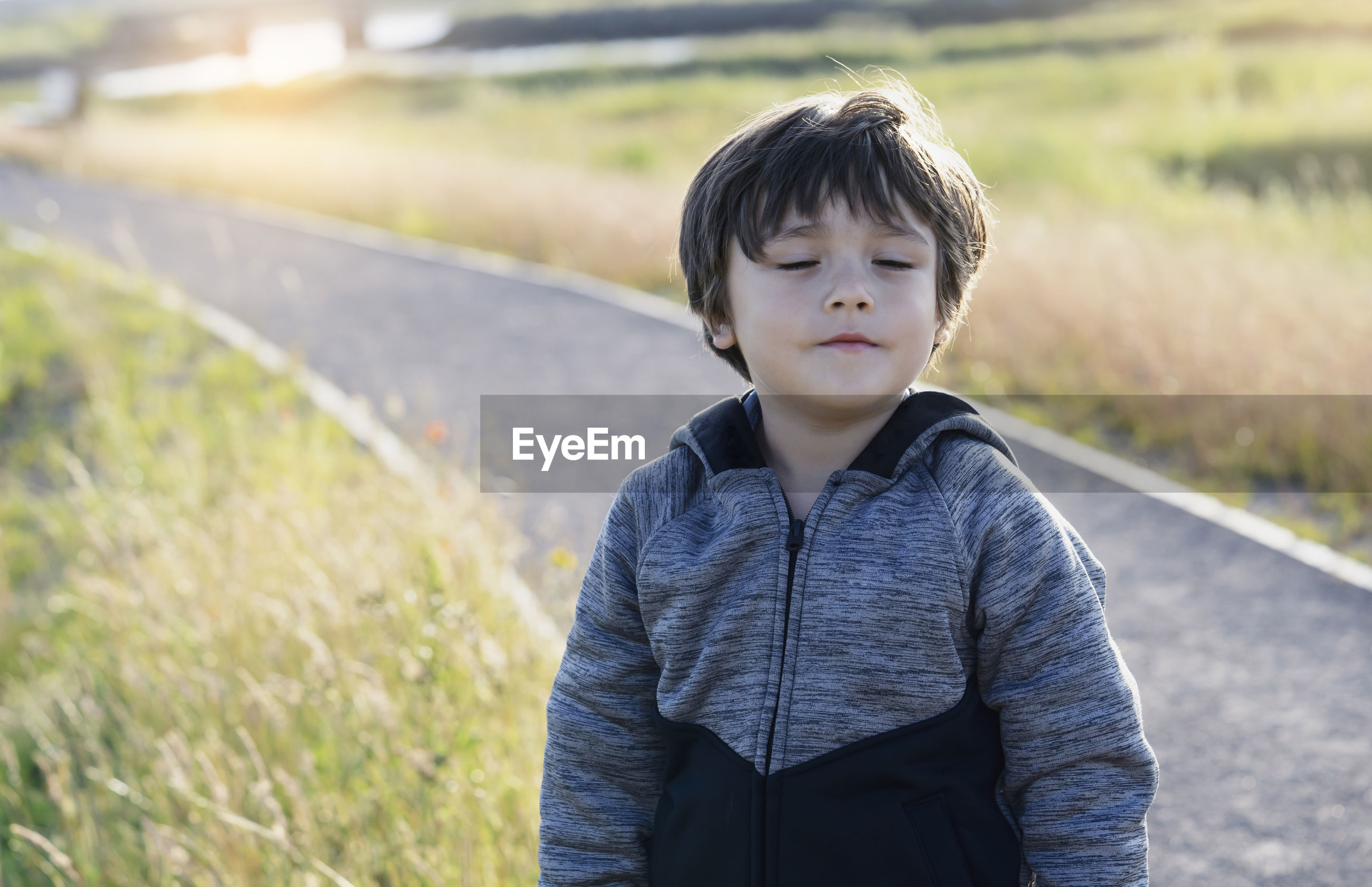 Boy with eyes closed standing on land