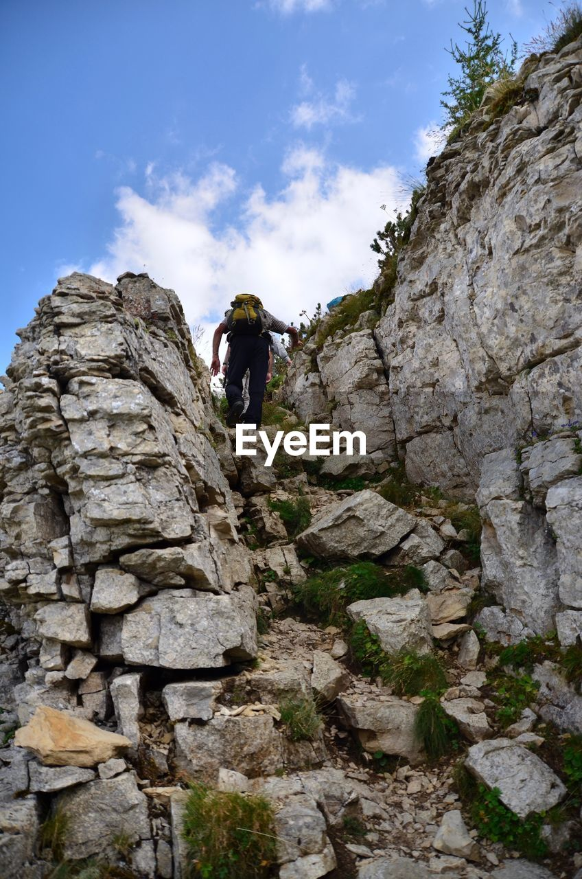 leisure activity, rock, one person, adventure, solid, rock - object, full length, climbing, real people, lifestyles, low angle view, nature, sky, day, rock formation, activity, young adult, adult, extreme sports, outdoors, stone wall