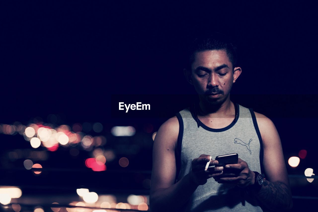mobile phone, wireless technology, night, portable information device, smart phone, communication, one person, front view, young adult, real people, holding, lifestyles, technology, illuminated, portrait, outdoors