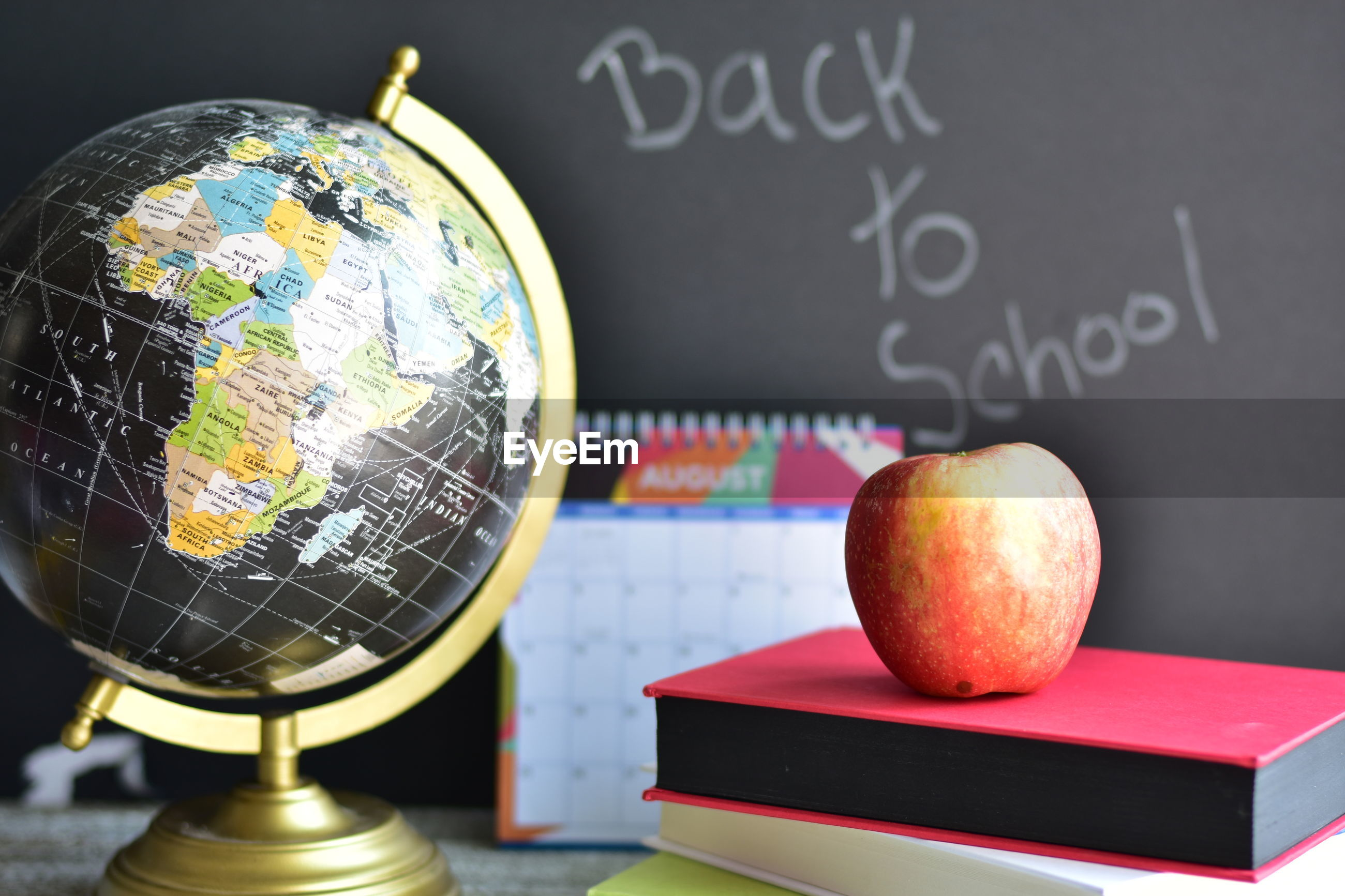 Close-up of apple over books by globe on table with text on blackboard in background