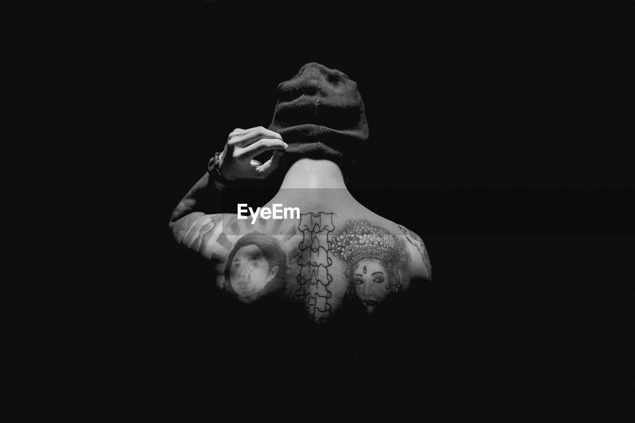 Close-up of shirtless man with tattoo against black background