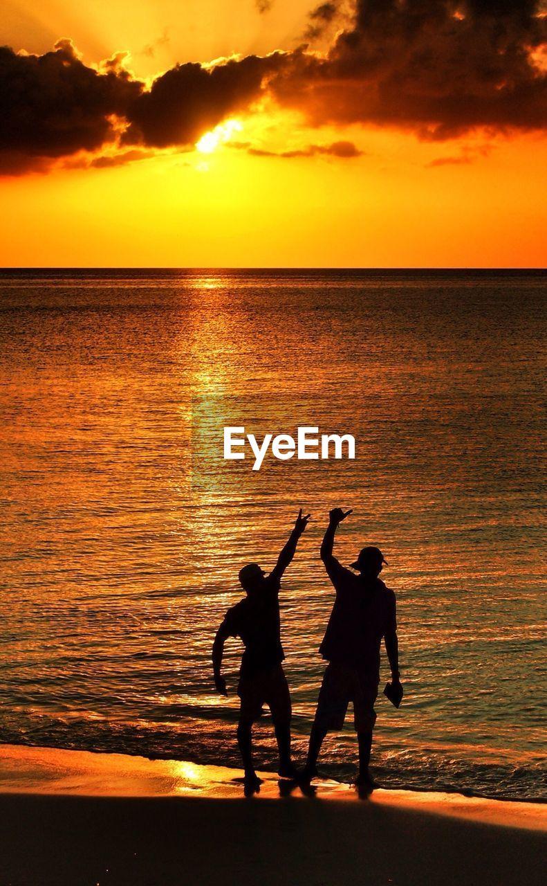 Silhouette friends enjoying on beach at sunset
