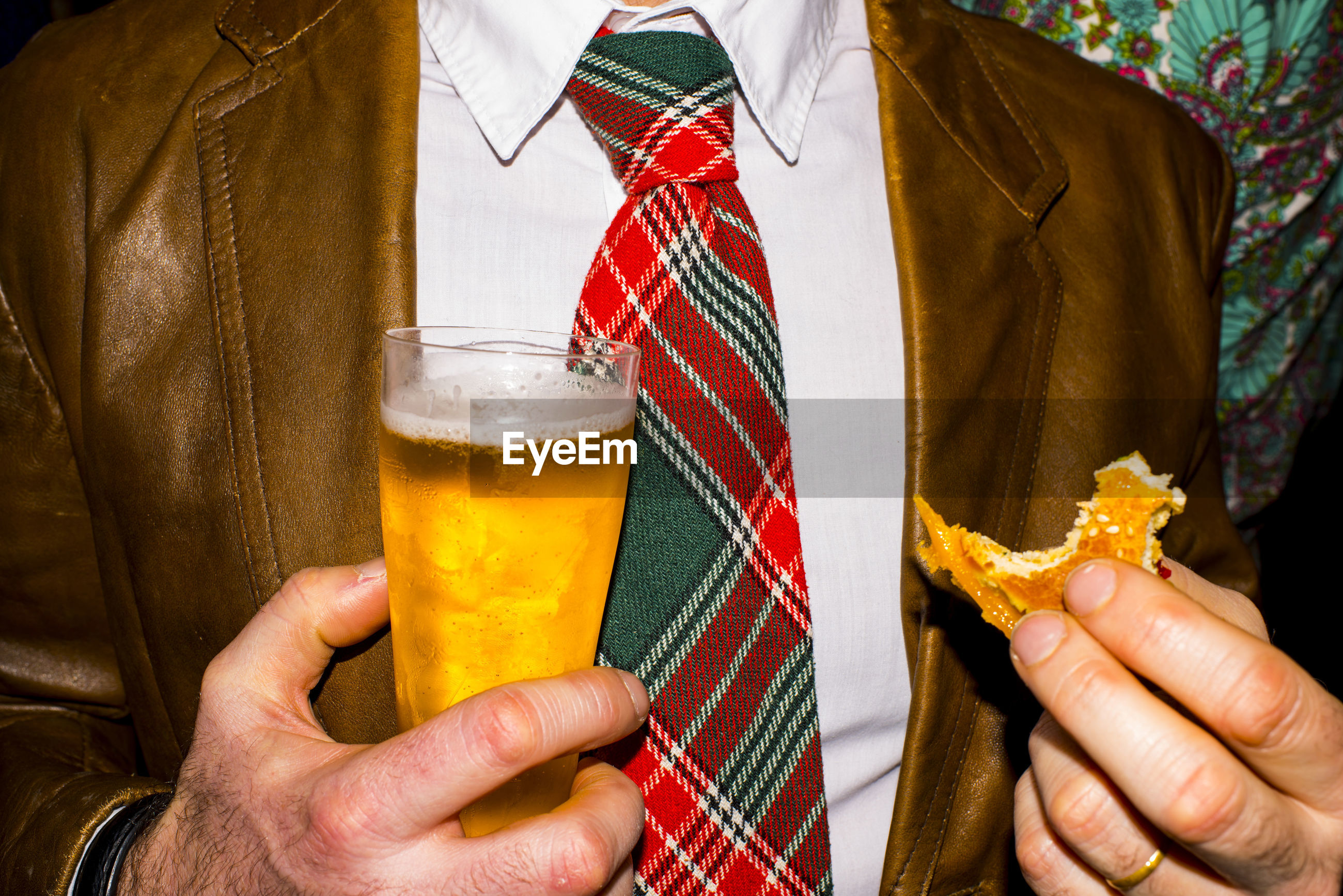 Midsection of man holding food and drink