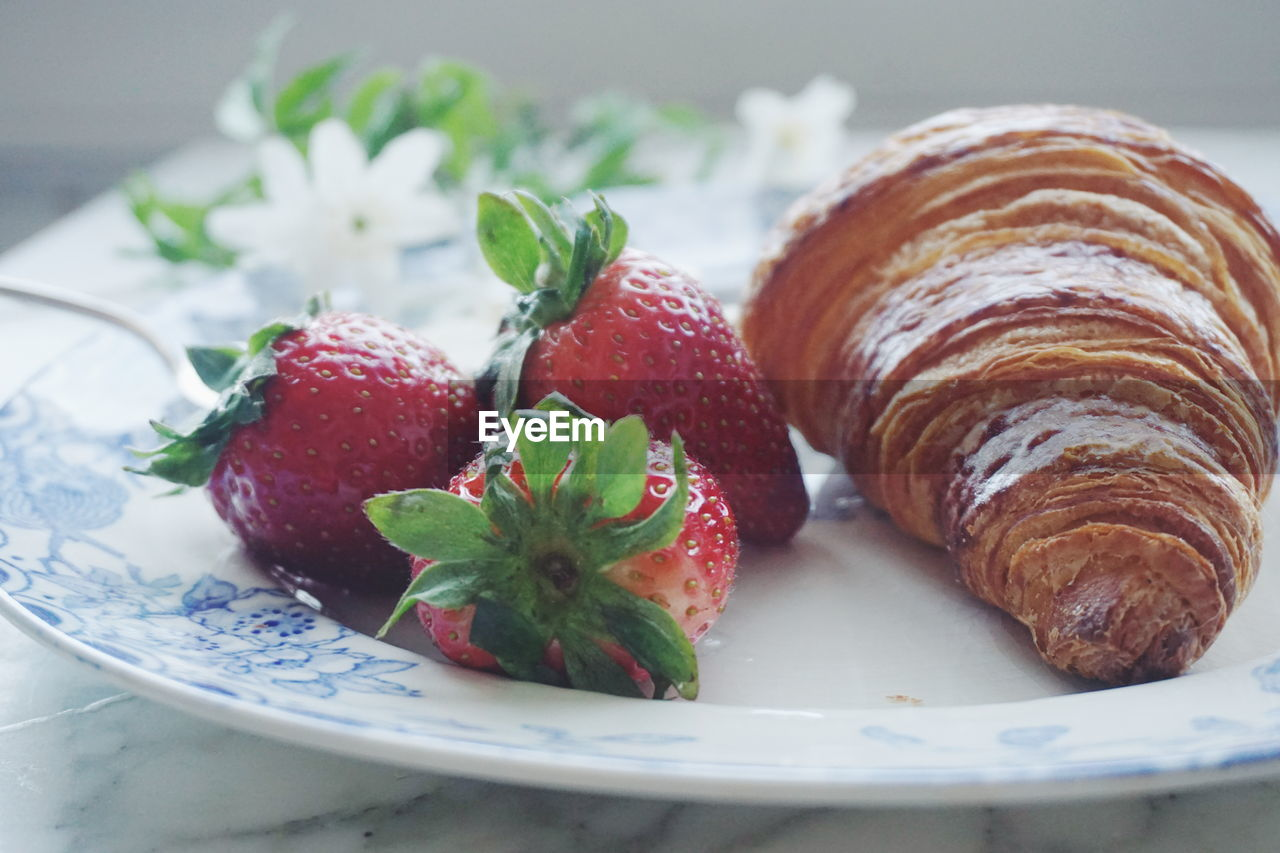 Close-up of strawberry with croissant in plate