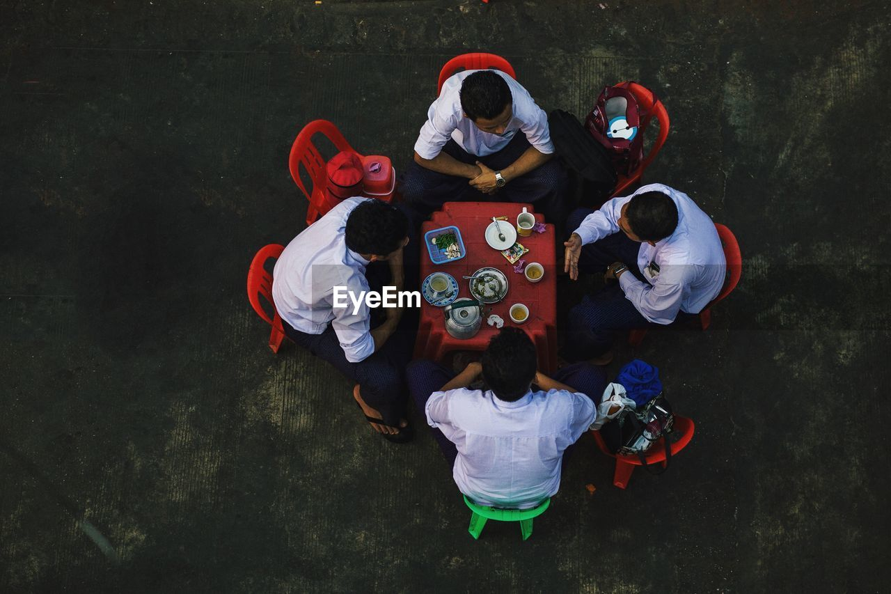 High Angle View Of Men Sitting On Chairs Over Floor
