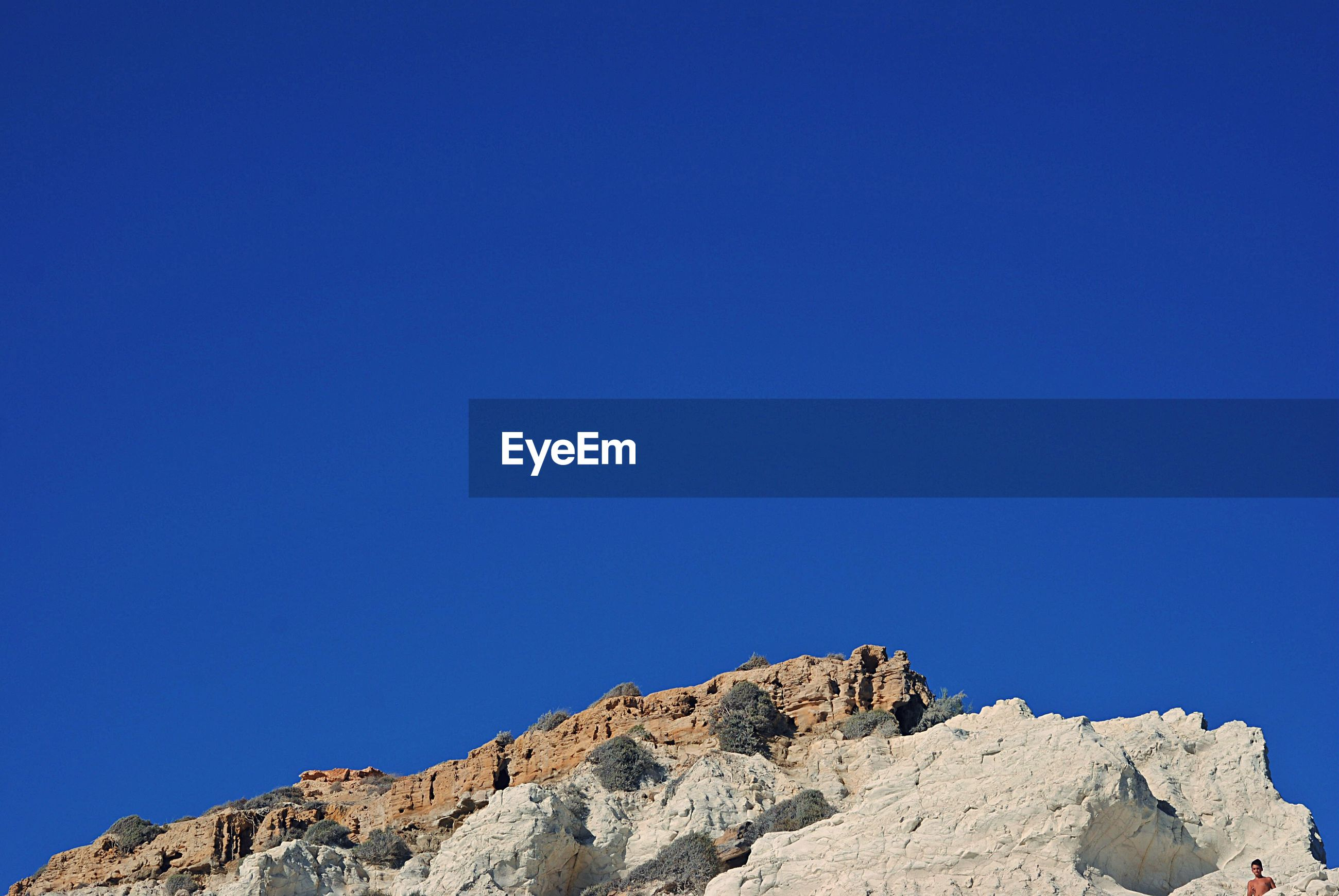 LOW ANGLE VIEW OF ROCKS ON MOUNTAIN AGAINST BLUE SKY