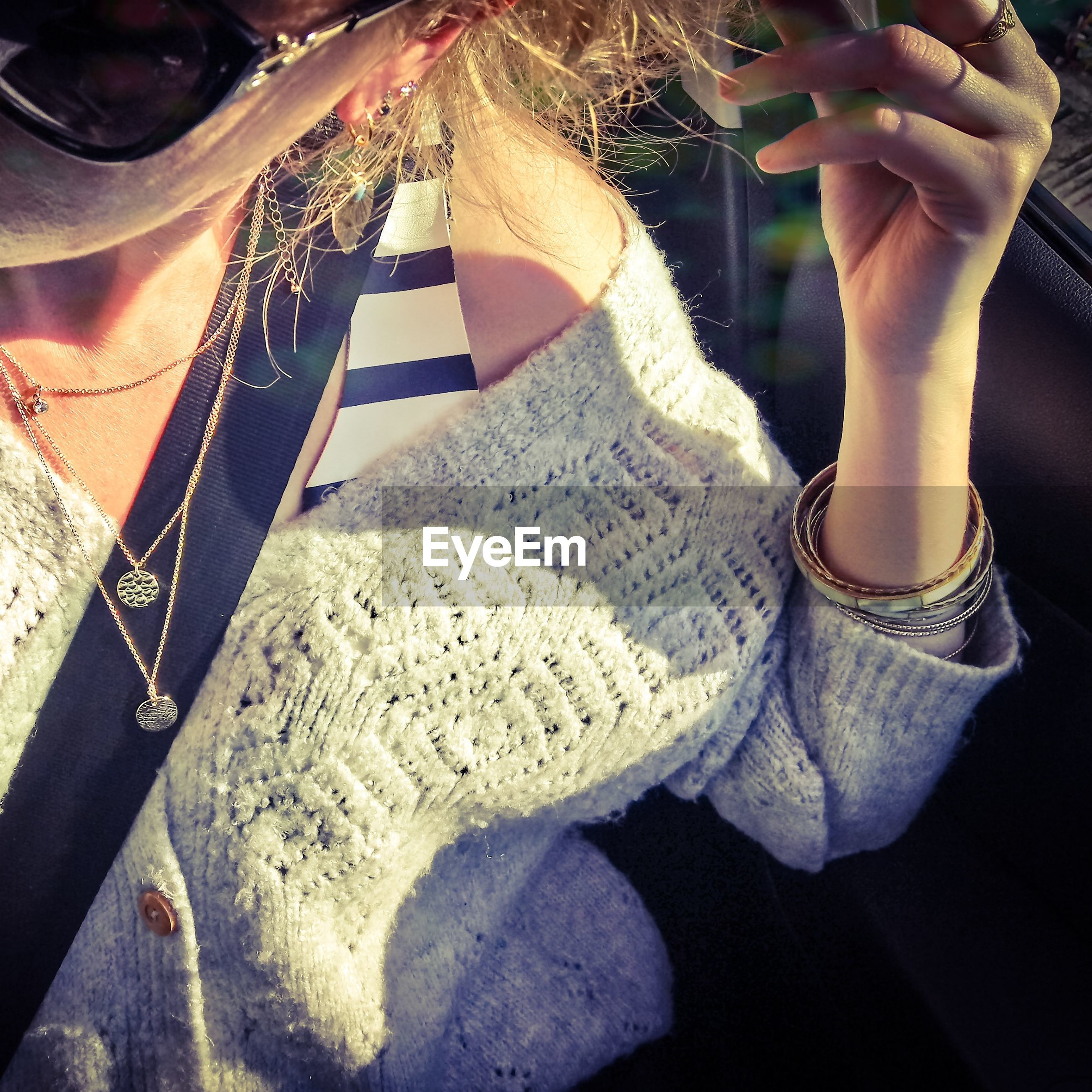 Midsection of woman wearing sunglasses in car