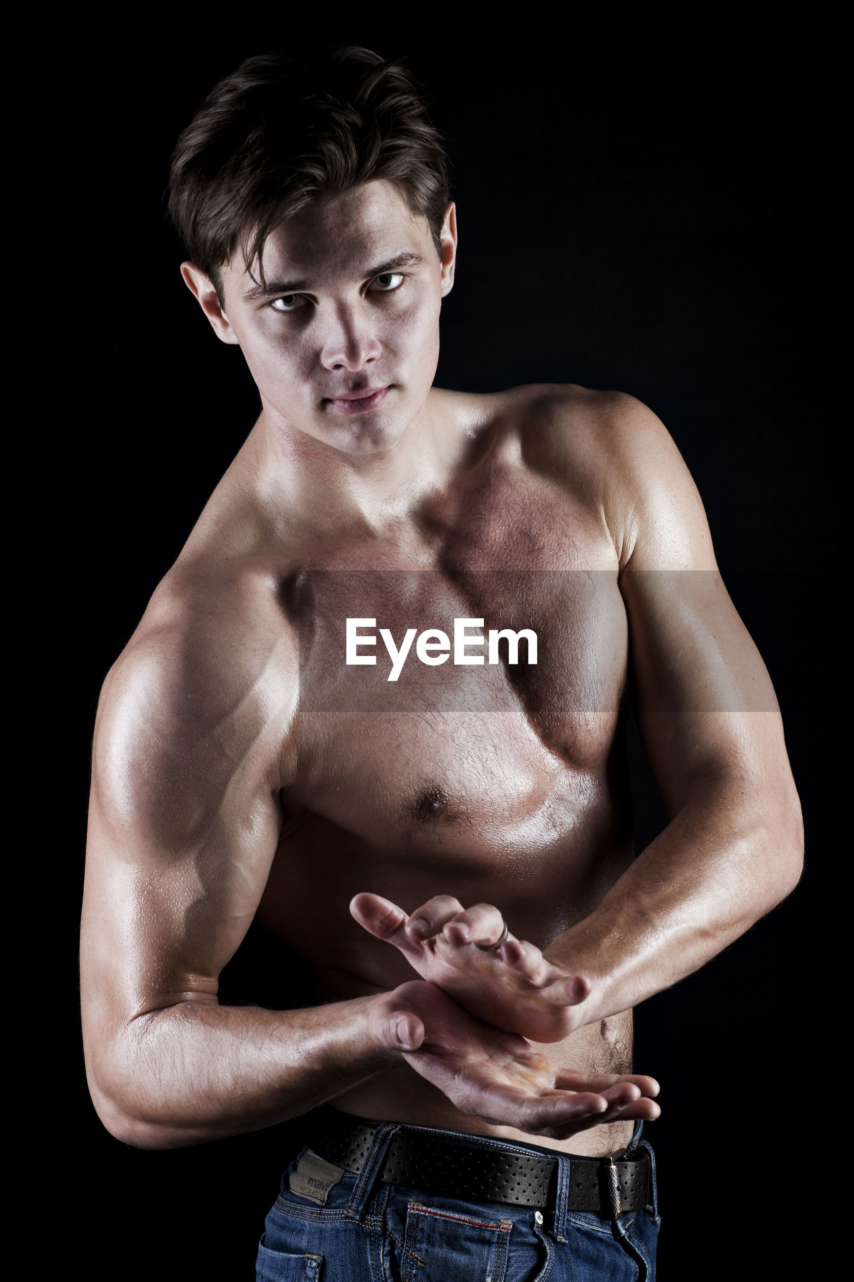 Portrait of young muscular man against black background