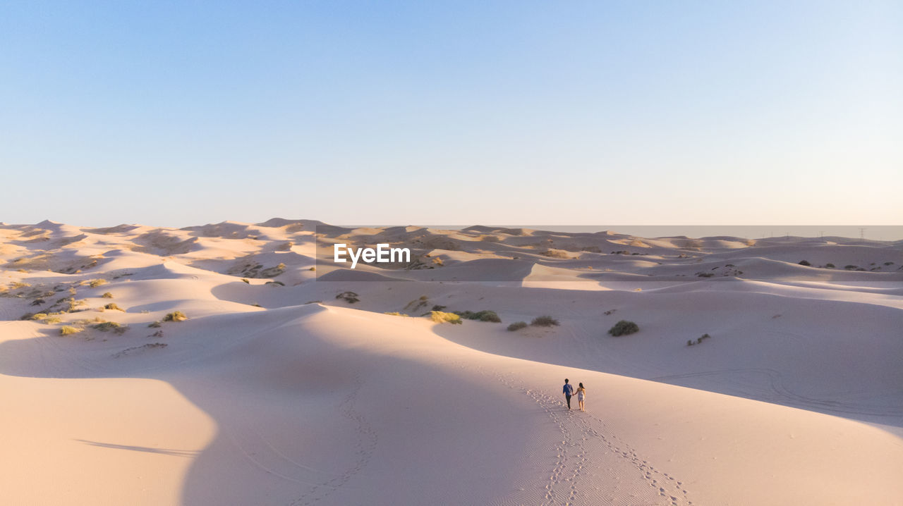 High Angle View Of Couple Walking On Sand At Desert Against Sky