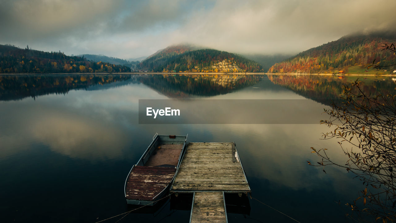 Boat moored by jetty on lake against cloudy sky