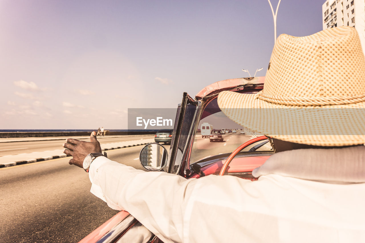 Rear View Of Man Driving By Beach Against Sky