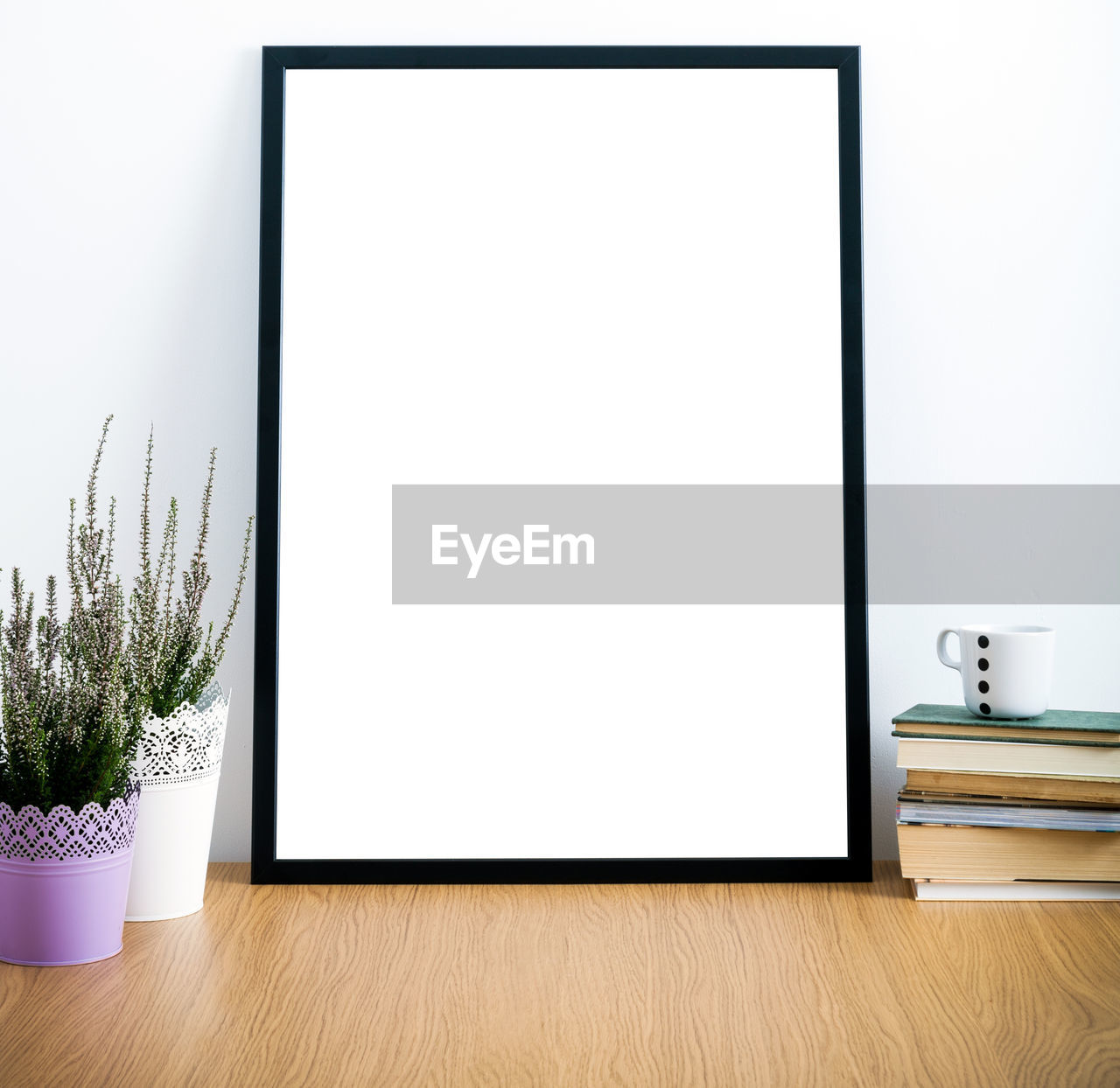 Empty picture frame by books and houseplants on table