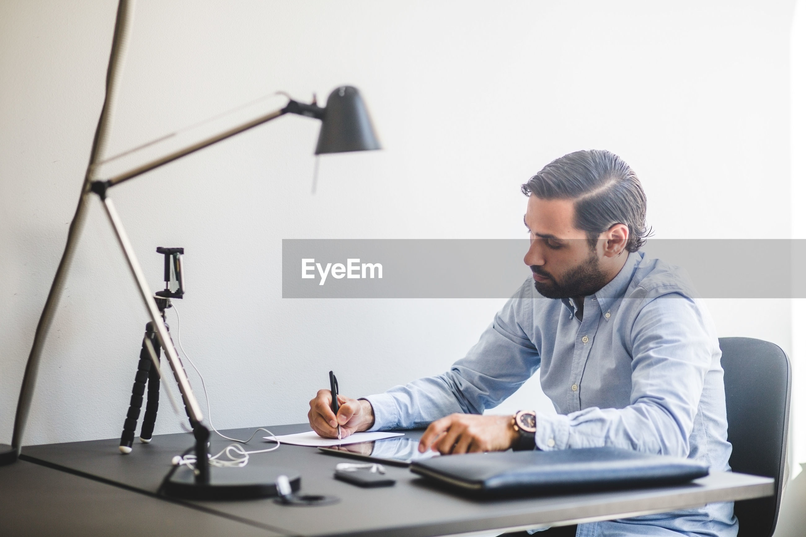 SIDE VIEW OF MAN WORKING ON TABLE IN OFFICE