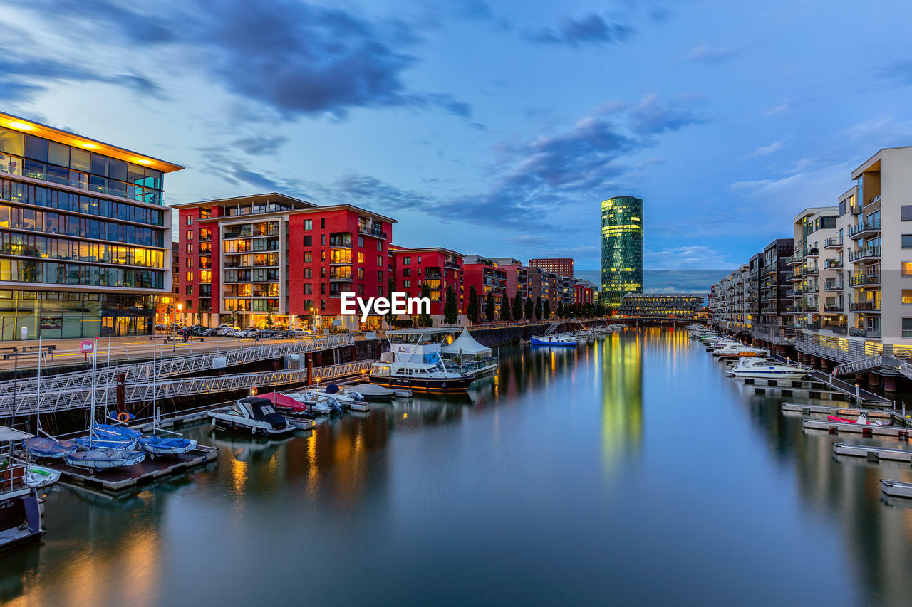 water, architecture, building exterior, sky, built structure, reflection, cloud - sky, waterfront, city, nautical vessel, transportation, moored, nature, mode of transportation, building, no people, river, harbor, outdoors, office building exterior, skyscraper
