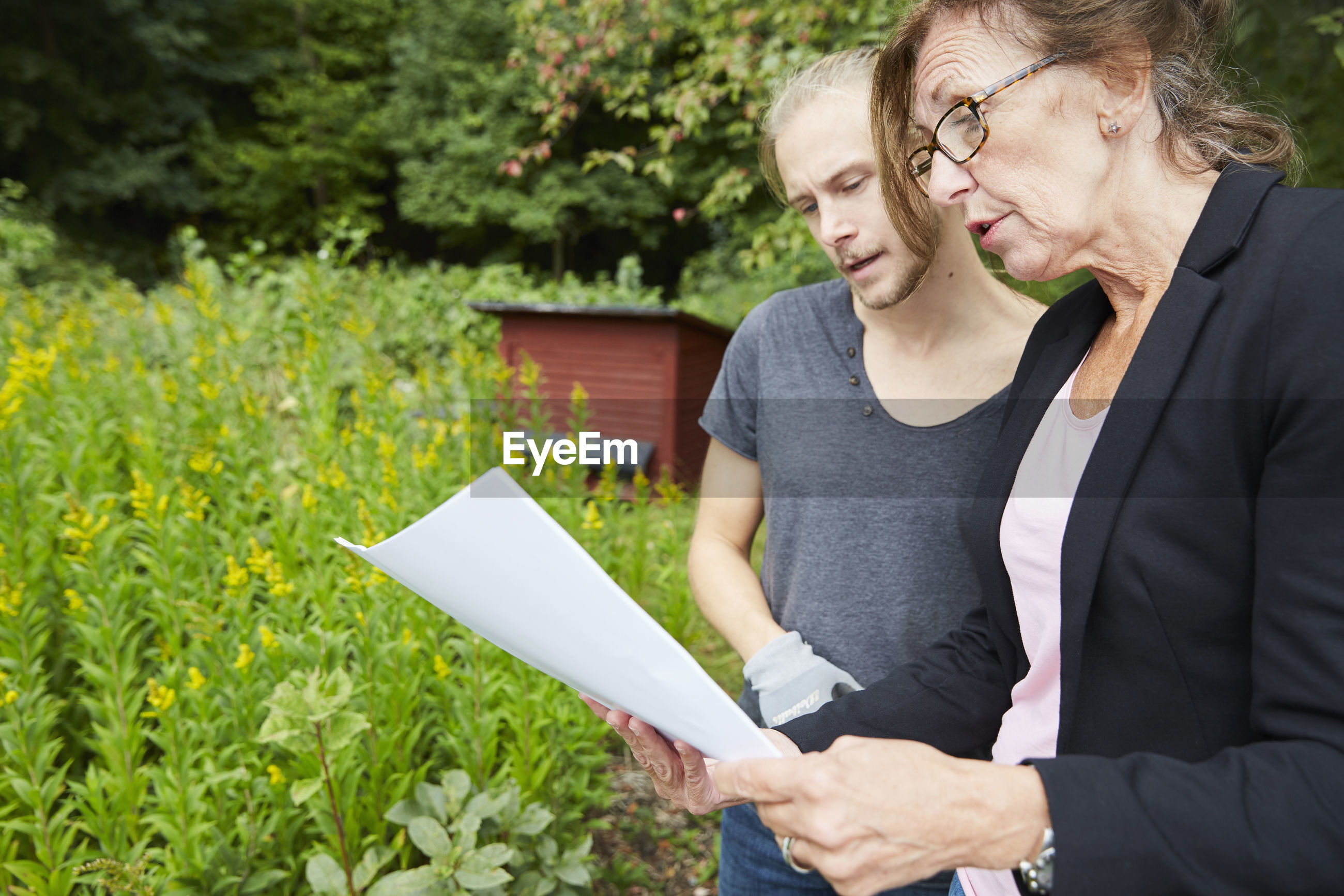 MIDSECTION OF MAN HOLDING WOMAN STANDING ON PLANTS