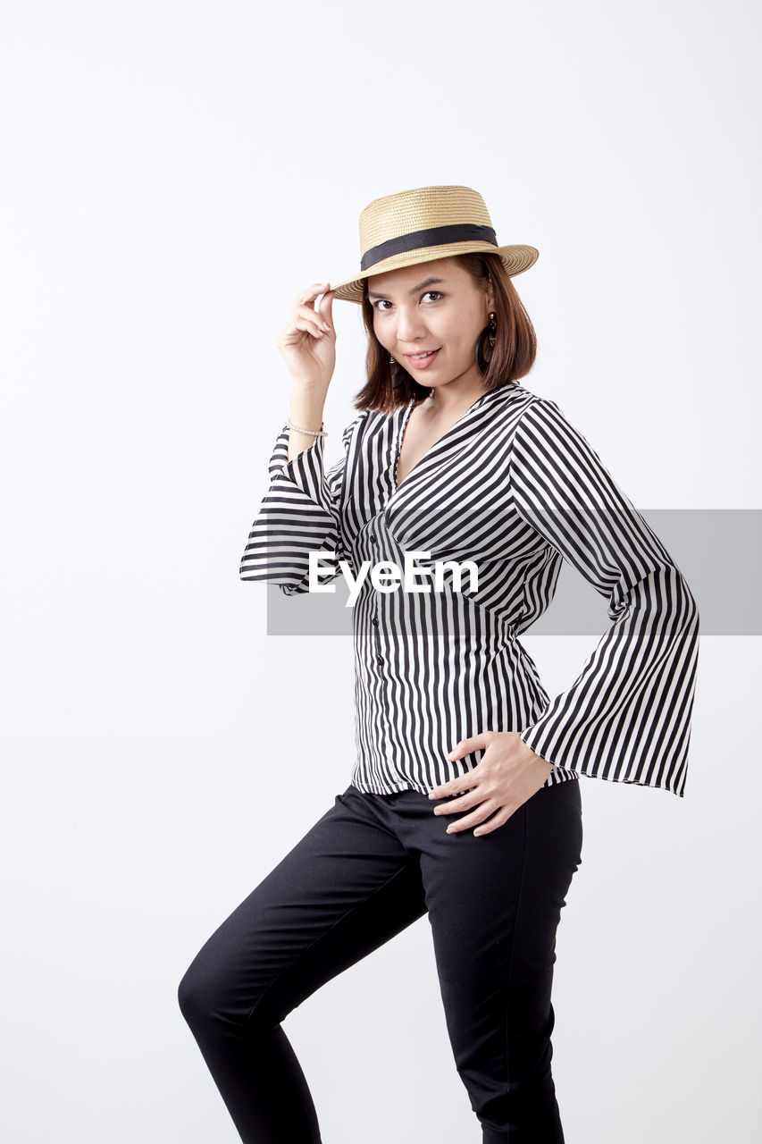 studio shot, one person, white background, clothing, indoors, striped, young adult, three quarter length, hat, young women, standing, beauty, cut out, casual clothing, beautiful woman, front view, women, lifestyles, fashion, hairstyle
