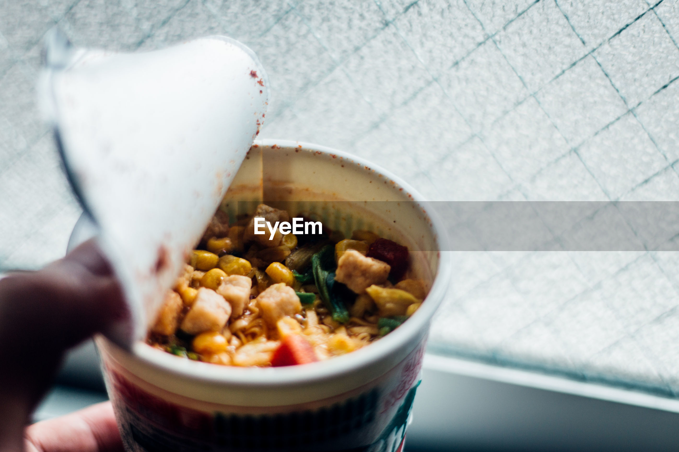 Cropped fingers of person holding food in container by window