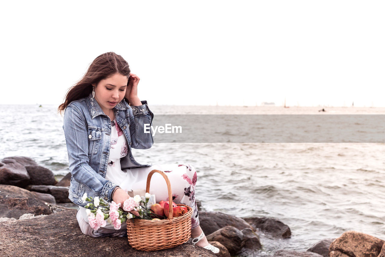 Young woman with wicker basket sitting on rock at beach against clear sky