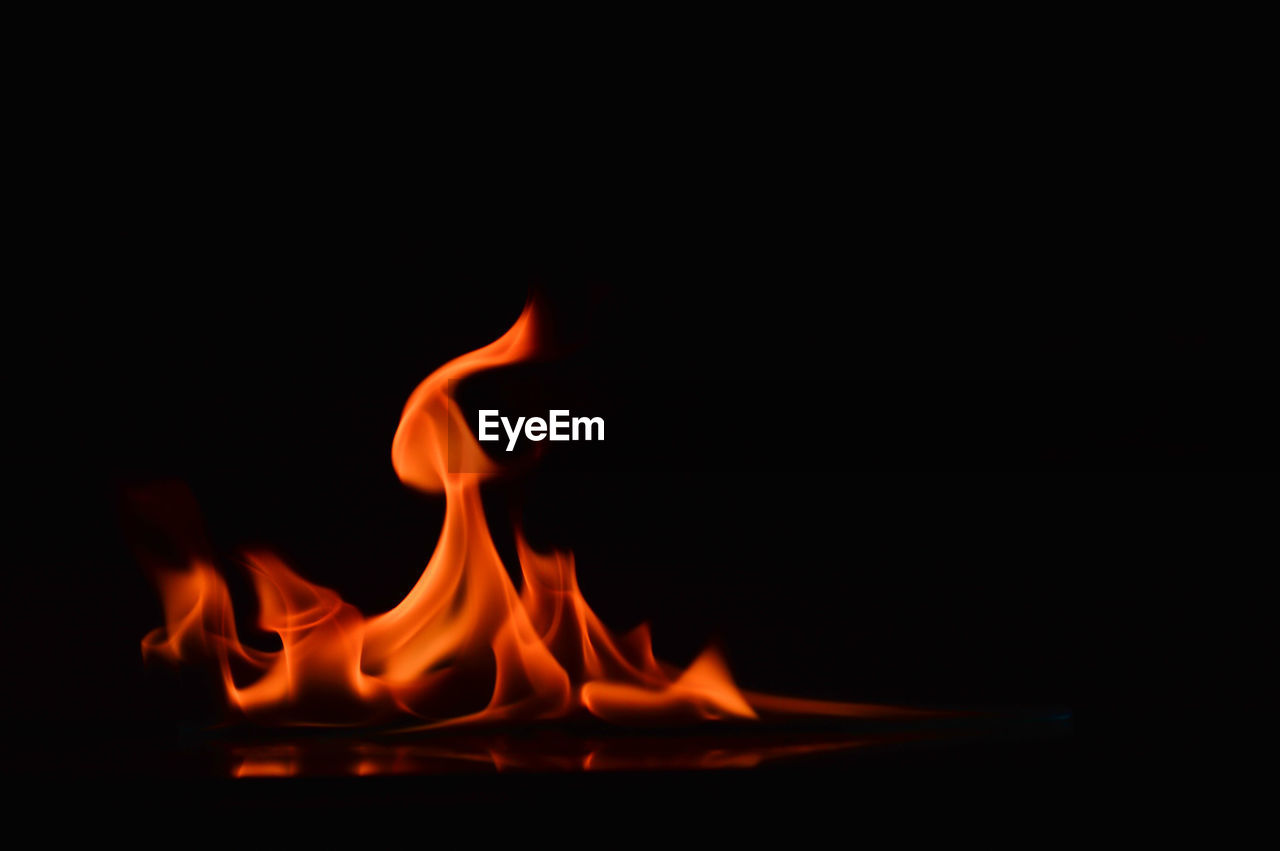 flame, burning, fire, fire - natural phenomenon, heat - temperature, motion, copy space, glowing, black background, orange color, nature, no people, indoors, studio shot, close-up, long exposure, dark, blurred motion, wood - material, environment, bonfire