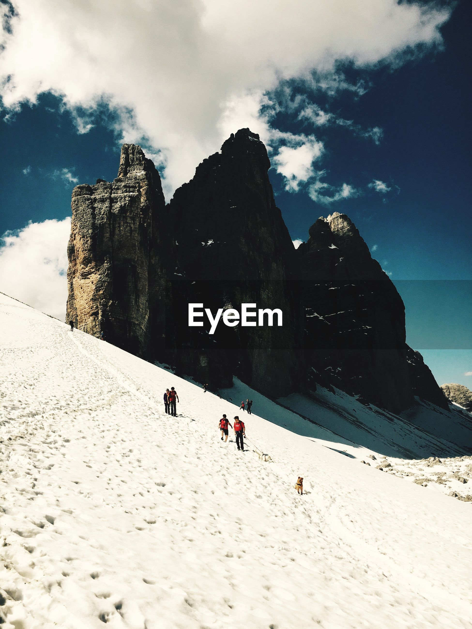 Low angle view of people on snowcapped mountain against cloudy sky