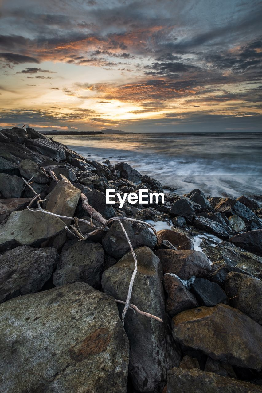 sea, sky, water, rock, solid, cloud - sky, sunset, rock - object, beach, beauty in nature, land, horizon over water, scenics - nature, horizon, nature, tranquility, motion, tranquil scene, no people, outdoors, rocky coastline