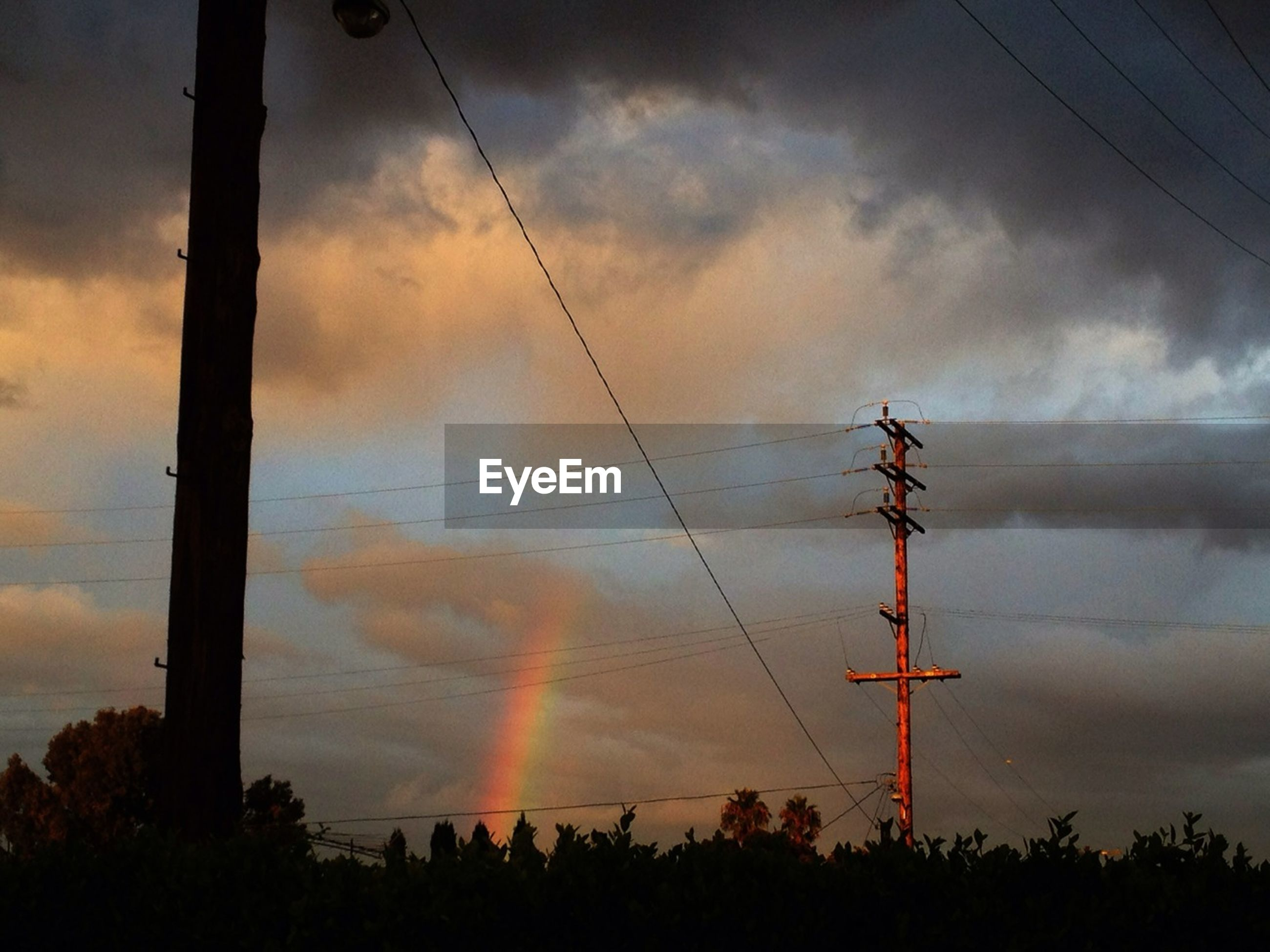 Low angle view of electricity pylon against cloudy sky at dusk