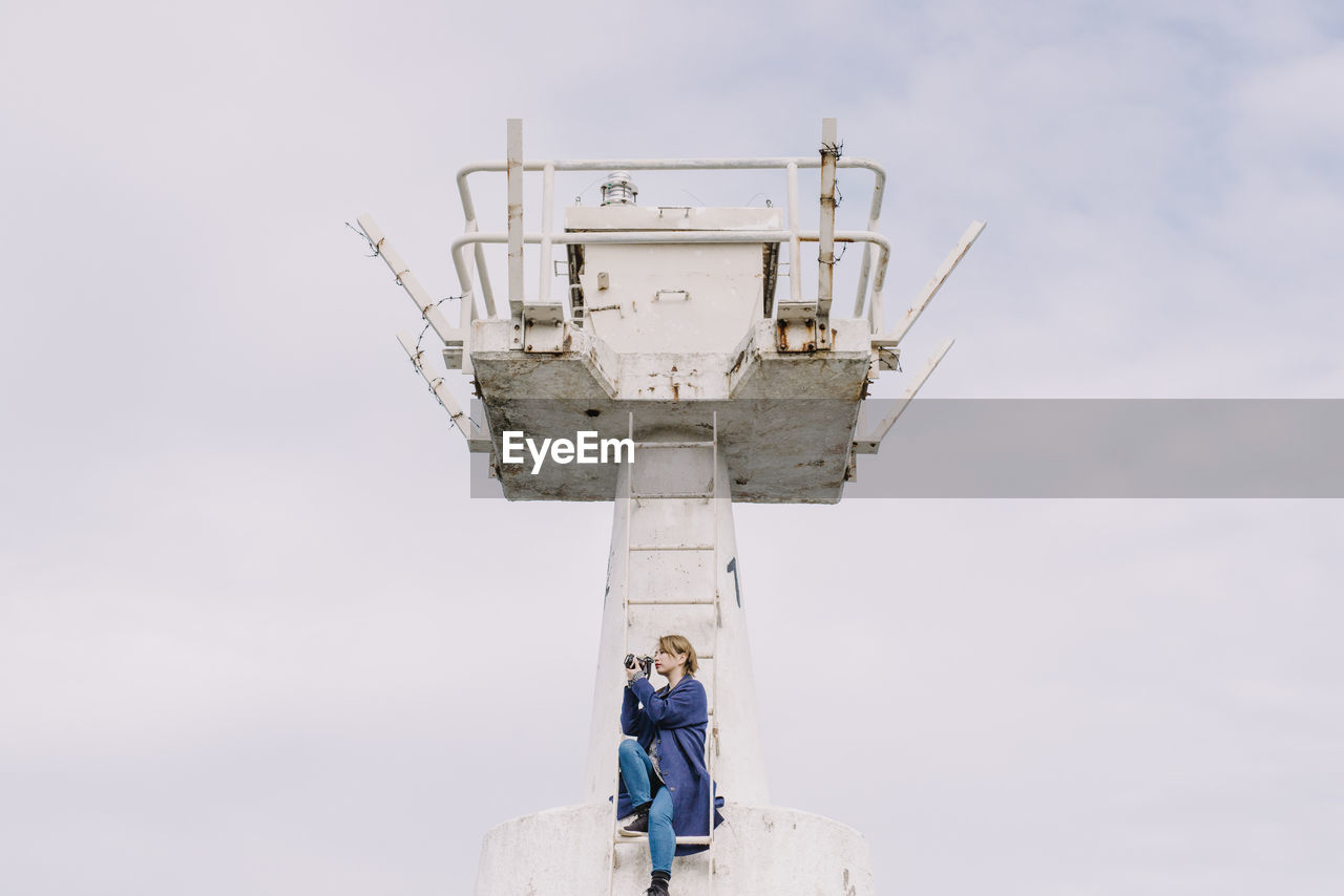 Low angle view of woman photographing while sitting on ladder at lookout tower against sky