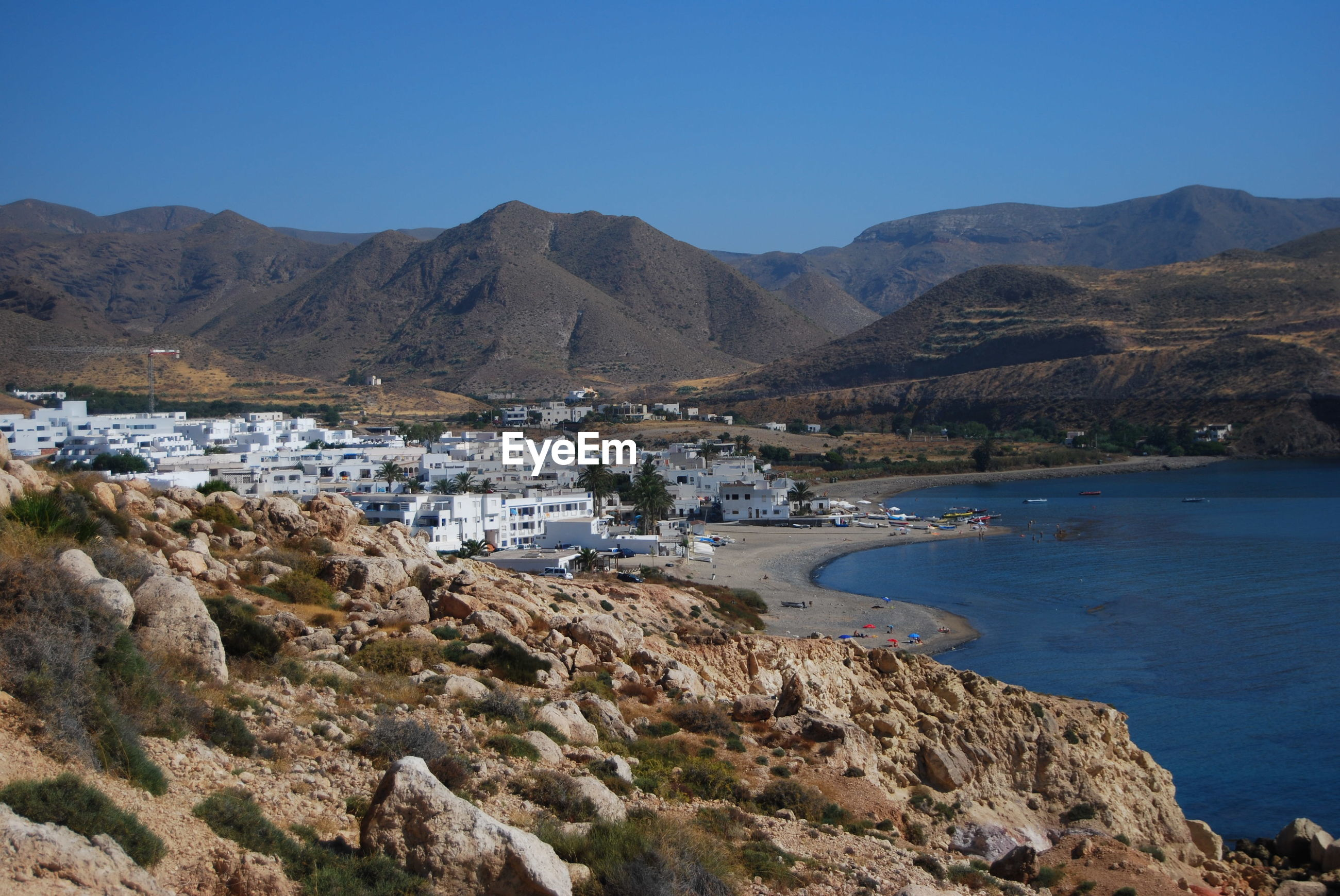SCENIC VIEW OF MOUNTAINS BY SEA AGAINST CLEAR BLUE SKY