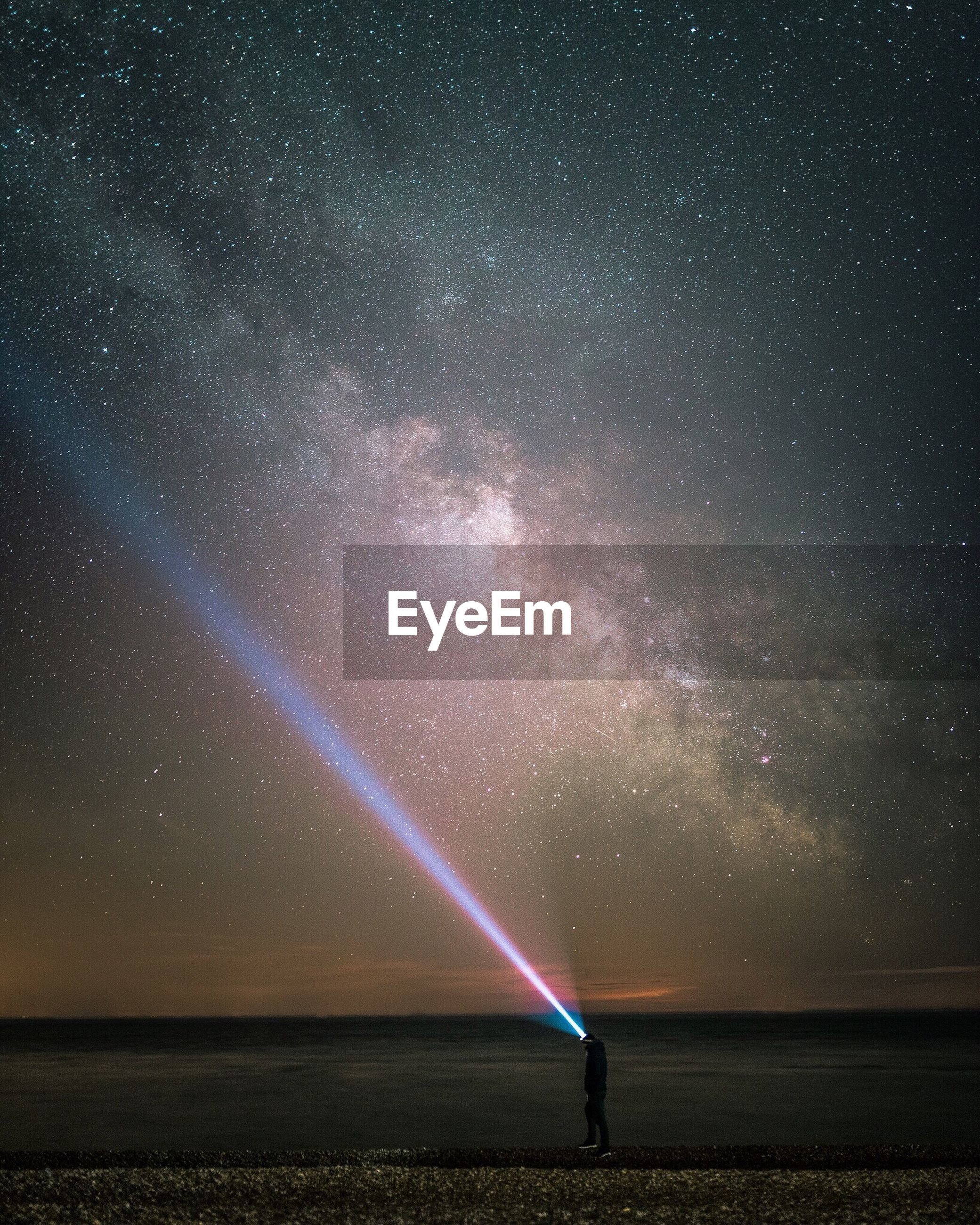 Person lighting sky with flashlight against star field at night