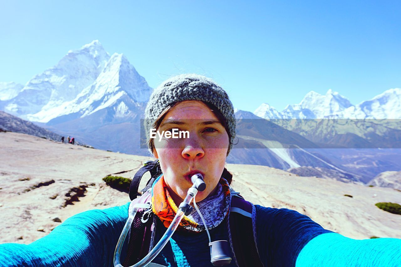 Portrait Of Woman With Pipe In Mouth Against Snowcapped Mountains