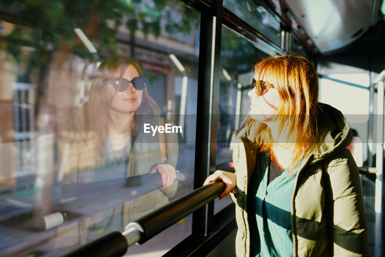 Woman wearing warm clothing while looking through window in bus