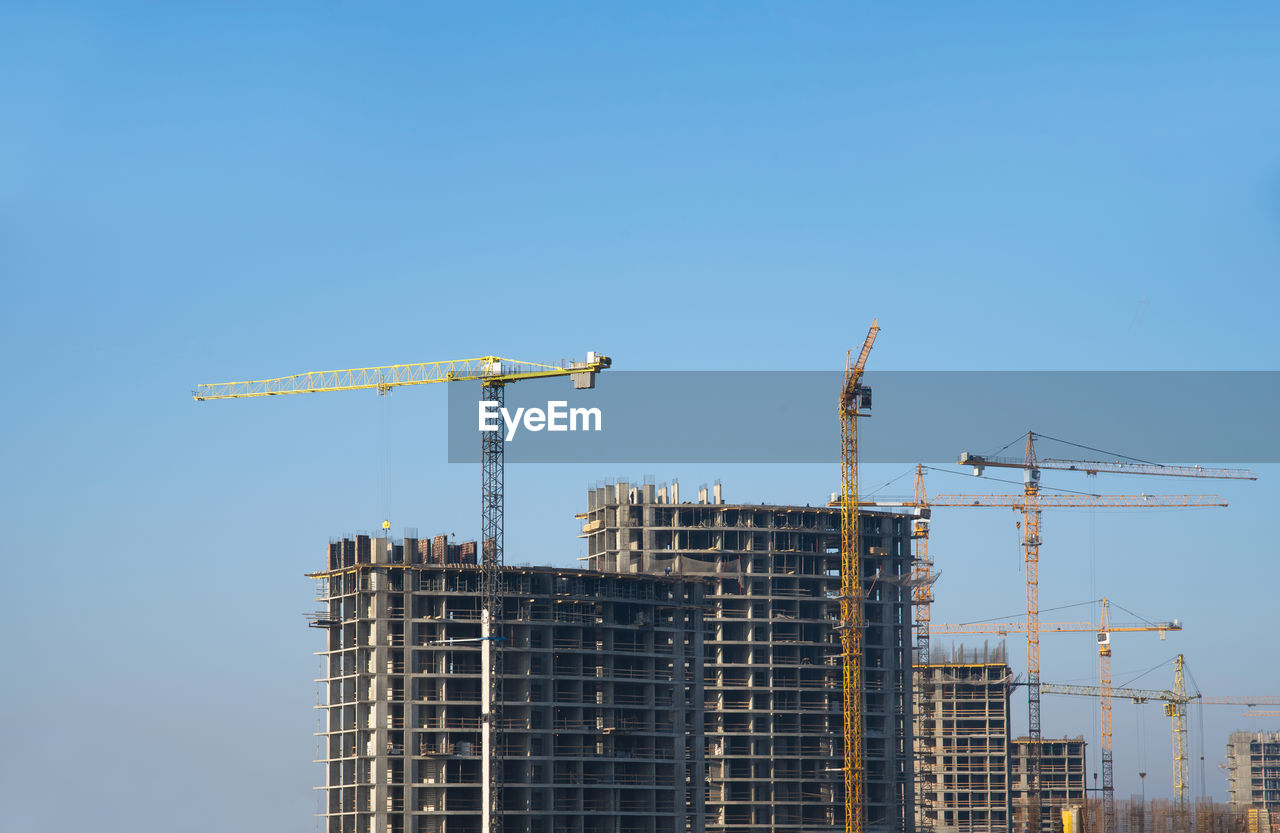 Low angle view of cranes on building against clear blue sky