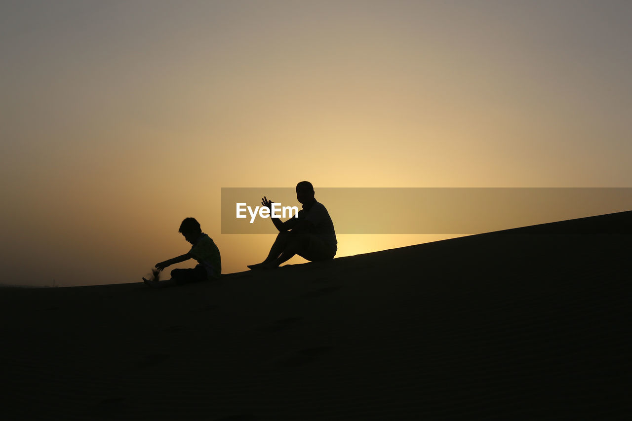Silhouette Of Father And Son Sitting On Sand