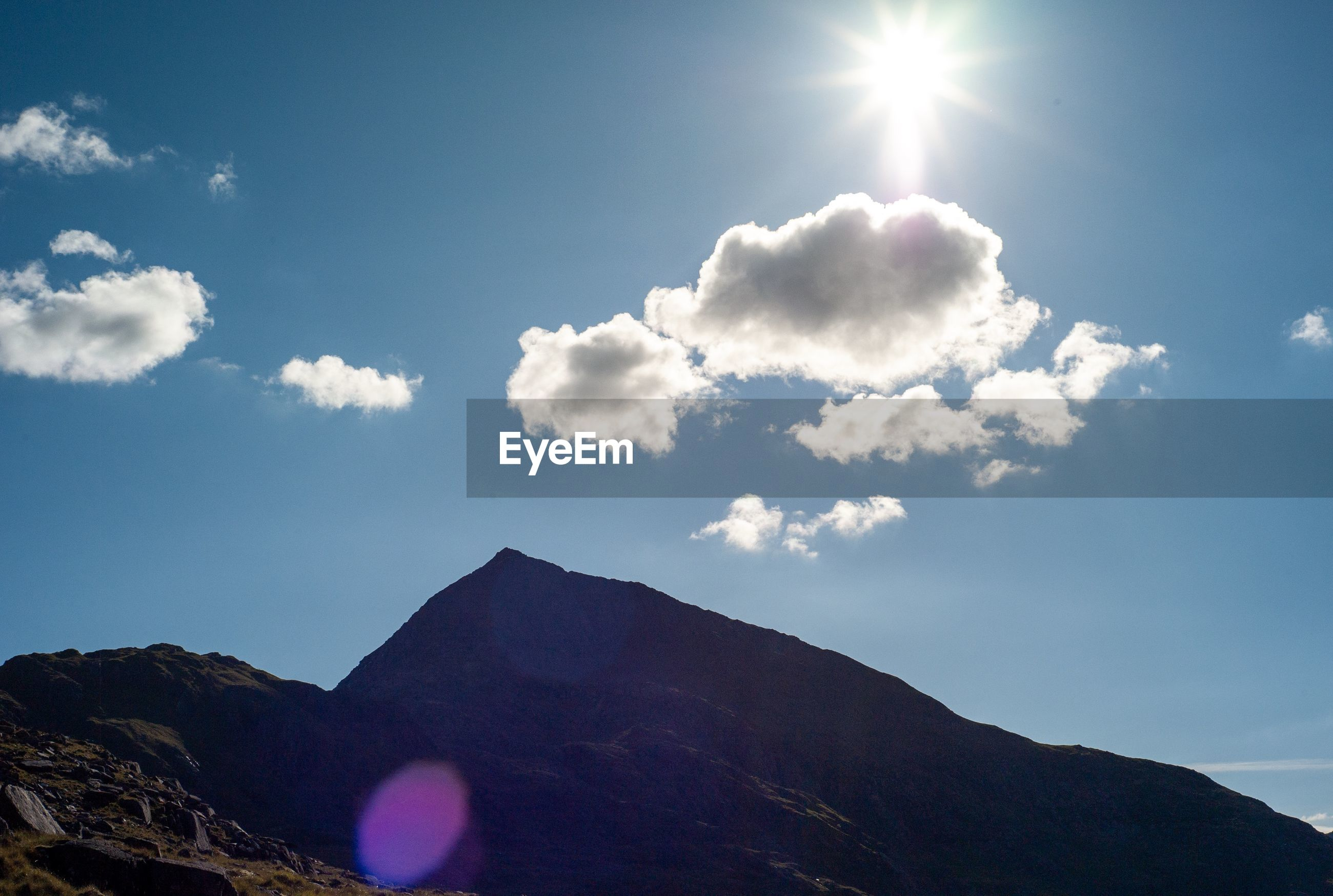 Low angle view of mountains against sky on sunny day