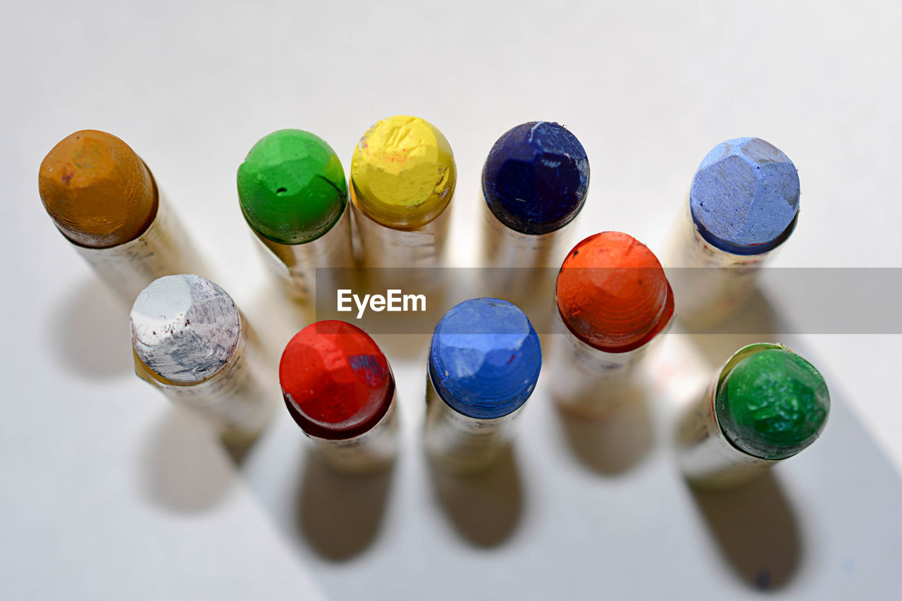 High angle view of multi colored crayons over white background