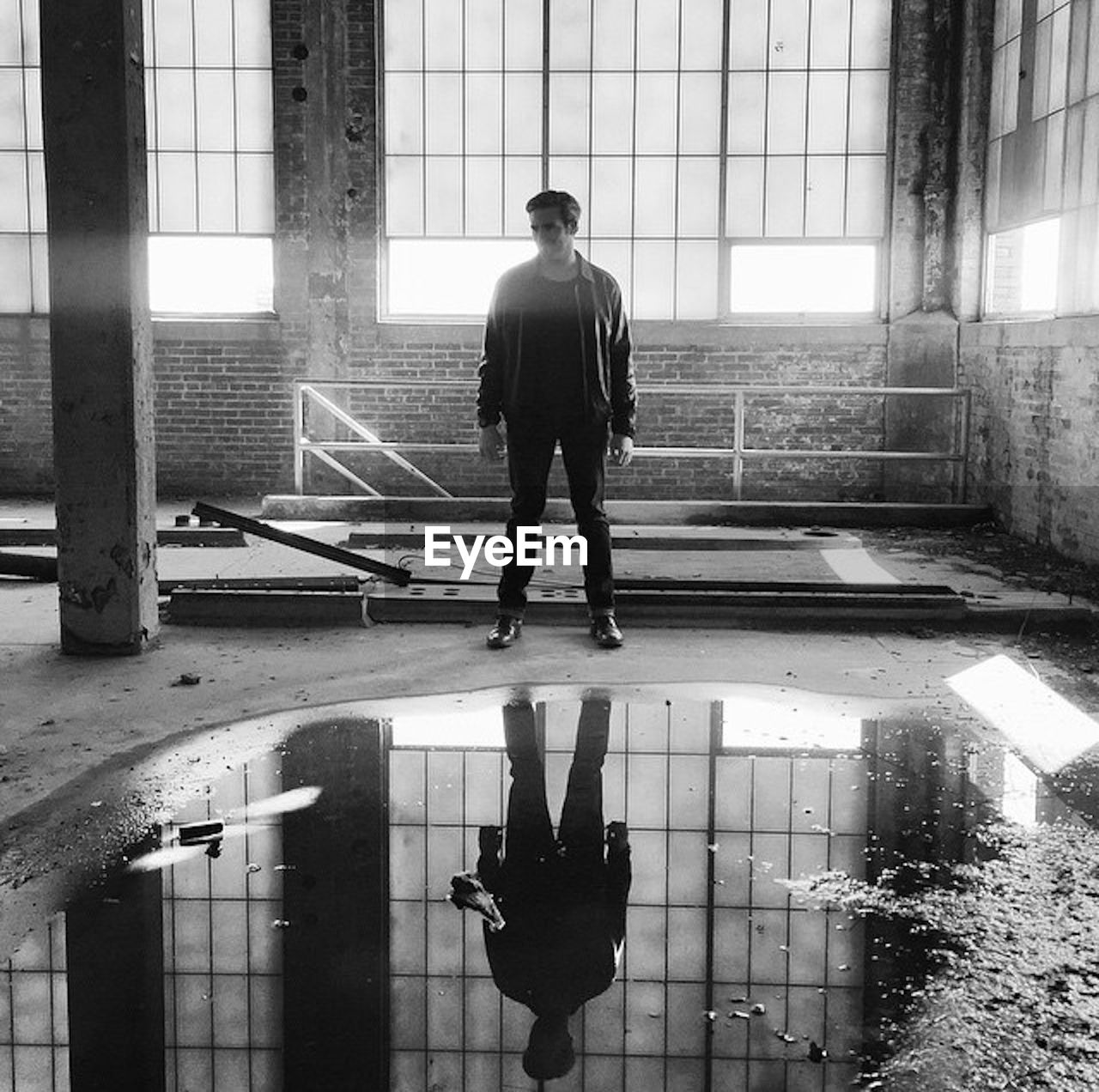 Man Standing By Puddle In Abandoned Building